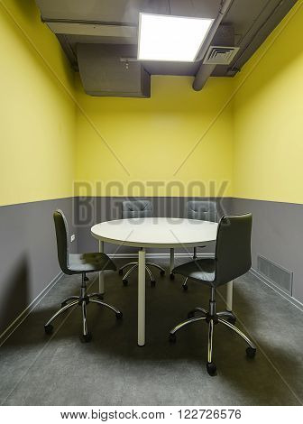 Room for meetings with gray and yellow walls. There is a round gray table with four chairs around it. On the floor there are gray tiles. At the top there are communications and a lamp.
