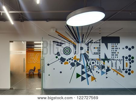 White wall with color prints and inscription. On the left there is an entrance to a meeting room with a translucent door with inscription on it. Room has  orange wall and chairs. On the floor there are gray tiles. At the top there is a big round lamp and