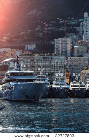 Monte Carlo, Monaco - September 20, 2015: yacht white modern vessels at moorage in sea port on sunny summer day against mountains light spot on cityscape background, vertical picture