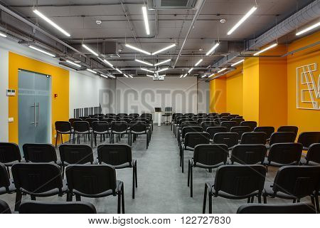 Room for lecture with a lot of chairs. Chairs are gray with black. Left and back walls are white, right wall is orange. On the left wall there are translucent doors with orange colored frame. There is a screen on the back wall. Near the screen is a table