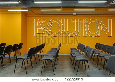 Room for lecture with a lot of chairs on the orange wall background. Chairs are gray with black. On the wall there is a white volumetric inscription. On the floor there are gray tiles. At the top there are communications and lamps.