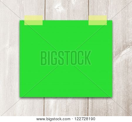 Bulletin Board with  green blank sticker. Green paper label with adhesive tapes on wooden background.