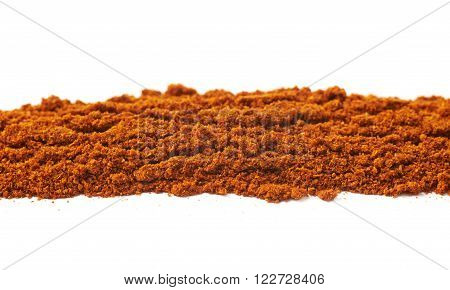 Line of a powdered red cayen pepper seasoning isolated over the white background