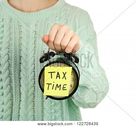 Woman in knitted sweater holding alarm with tax time inscription, isolated on white