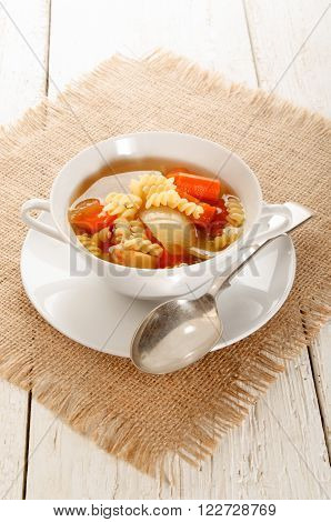 soup with carrot onion and penne rigate in a bowl
