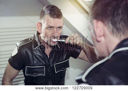 man in black fetish leather gear brushing his teeth