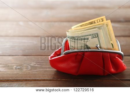 Purse with dollar on wooden background