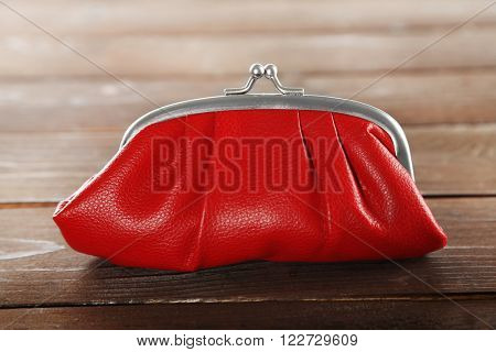 Red leather purse on wooden background