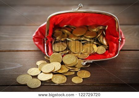 Coins in red purse on wooden background
