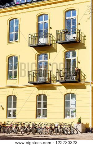 Kalmar Sweden - March 17 2016: Female person basking in the warm sunshine on a balcony of a yellow building. Bikes on the ground below. Real people in everyday life.