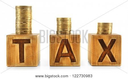 Stacked coins on wooden cubes with word TAX isolated on white