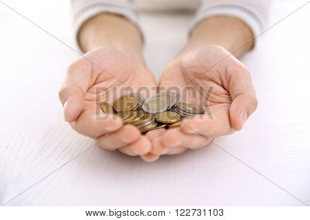 Man with handful of euro coins at the table on white background