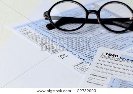 1040 Individual Income Tax Return Form with  black rimmed glasses isolated on the white background, close up