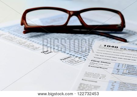 1040 Individual Income Tax Return Form with  brown rimmed glasses isolated on the white background, close up