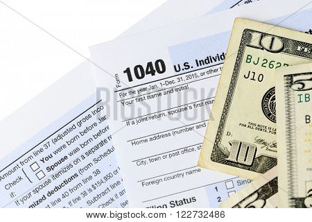 1040 Individual Income Tax Return Form with ten and five dollar bills on white background, close up