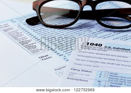 1040 Individual Income Tax Return Form with  black rimmed glasses close up