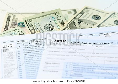 1040 Individual Income Tax Return Form with  dollar bills on white background, close up