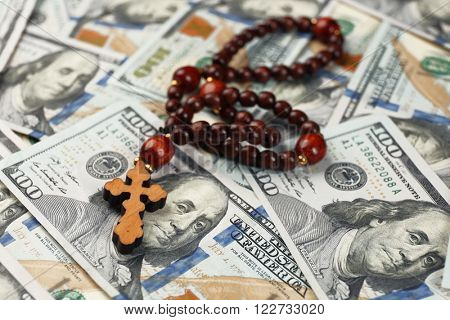 Rosary beads on money background, closeup