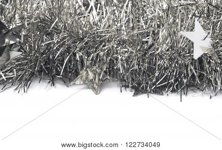 Close-up fragment of the silver tinsel garland decorations isolated over the white background as a copyspace backdrop composition