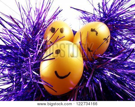 Plastic easter eggs with drawing happy smiling on faces on violet tuft for easter festival