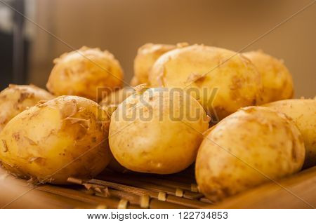 fresh raw potatoes close up on wood
