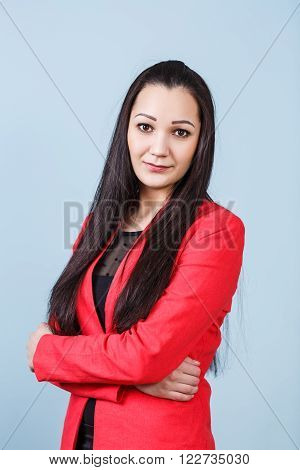 Young  beautiful woman with crossed hands on the blue background