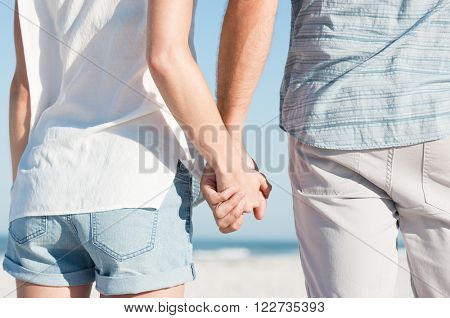 Close up of young couple holding hands at beach. Rear view of young couple holding hands and walking at beach. Closeup of two hands holding each other.