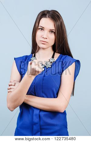 Strict beautiful woman shows threaten fist on the blue background