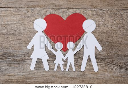 Top view of white paper chain family on red shape heart. Family in love. Family care and unity concept.