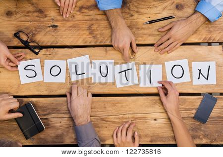 Businesspeople arranging placards on wooden table forming the word solution. White cards strategy used by businesspeople. Businesspeople find the right solution for their problem.