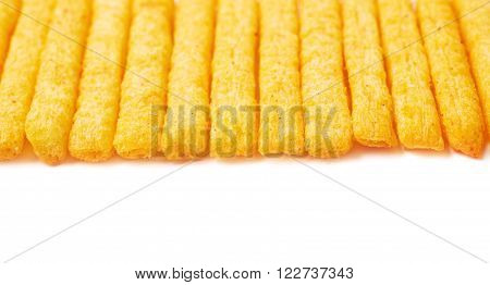 Multiple cheese puff stick corn snacks arranged in a line as a copyspace close-up crop backdrop, composition isolated over the white background