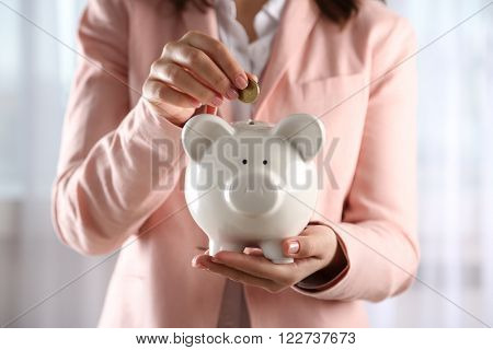 Woman holding on hands and putting coin into piggy bank, close up