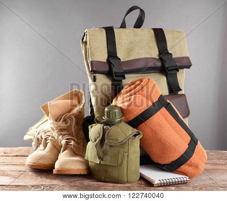 Tourism concept. Backpack, pair of boots and canteen on wooden table, against grey background