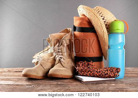 Tourism concept. Rug and plastic thermos on wooden table against grey background