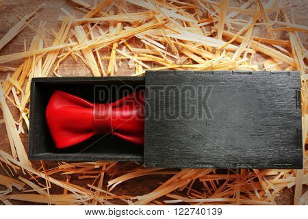 Red leather bow tie in a special packaging on a thatch, close up