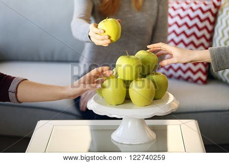 Female hands taking apples from the plastic stand