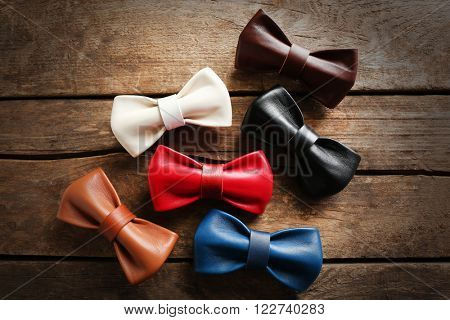 A set of colorful leather bow ties on a brown wooden background