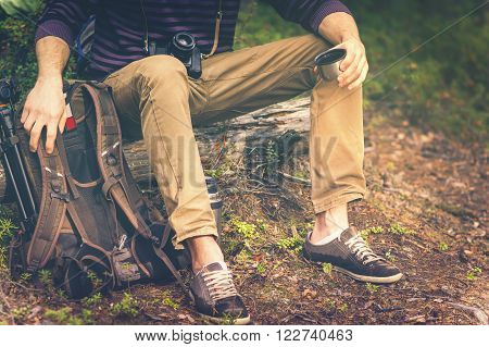 Traveler Man relaxing in forest with photo camera backpack and thermos drinking tea Travel Lifestyle concept vacations outdoor