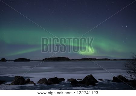 Scenic view of a moonlight frozen lake landscape with northern lights