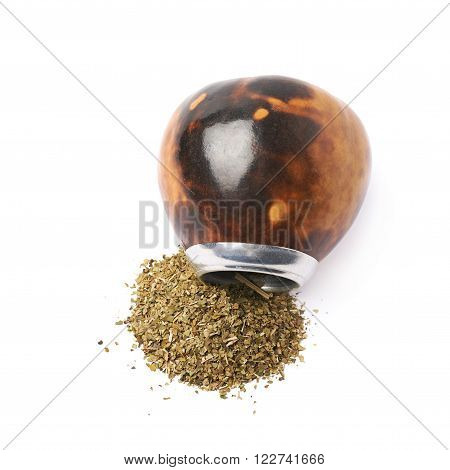 Calabash gourd vessel on top of a pile of dry mate tea leaves, composition isolated over the white background