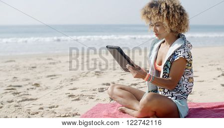 Woman Uses Touchpad Tablet On The Beach