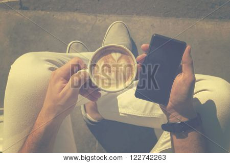 Hipster guy drinking coffee and using cellphone.