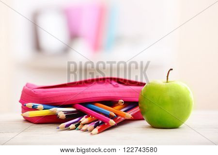 Apple and pencil-box full of pencils on table in the room