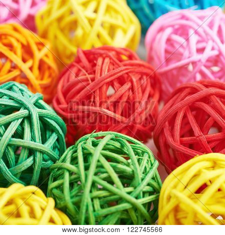 Surface covered with the multiple decorative and colored straw balls as an abstract background composition with a shallow depth of field