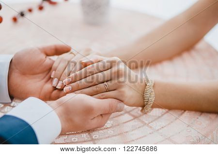 groom holding beautiful bride's hands with ring at table. Romanic concept before the wedding ceremony