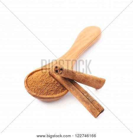 Wooden spoon full of cinnamon powder and raw bark sticks on top of it, composition isolated over the white background