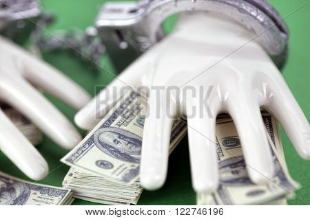 two white ceramic  hands with handcuffs on pile of 100 dollar notes on black background