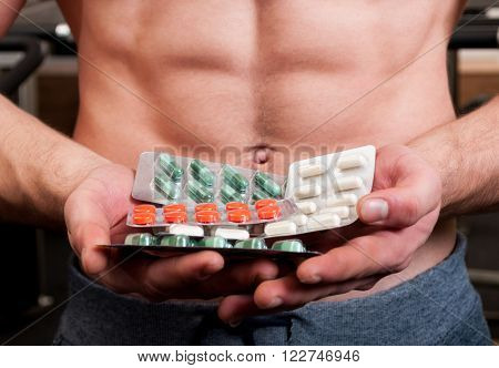 Muscle Man Holding Blisters Of Pills