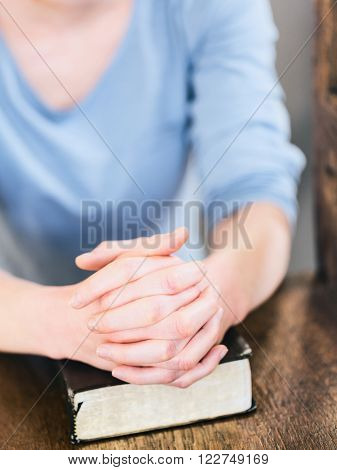 Young woman praying on a chair with a closed Bible.