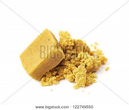 Crushed yellow bouillon stock broth cube isolated over the white background ** Note: Shallow depth of field